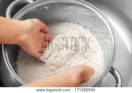 Woman rinsing rice in saucepan