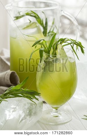 Homemade cold lemonade with Estragon tarragon leaves on white wooden table. wite background
