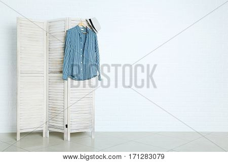 Male Shirt And Hat Hanging On Folding Screen On Brick Wall Background
