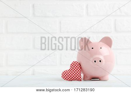 Pink piggy bank with red heart on white brick wall background