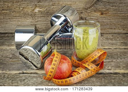 The concept of weight loss, smoothie and apple on wooden desk