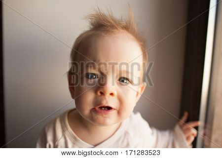 Portrait Of A Little Boy Who Is Sitting At The Window And Indignant. Emotions Concept