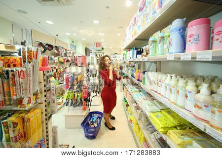 MOSCOW - OCT 14, 2016: Woman (with model release) with with shopping cart sniffs shampoo in Goods for Home shop