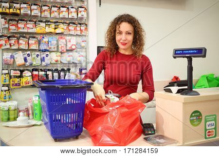 MOSCOW - OCT 14, 2016: Woman (with MR) packs purchase in Goods for Home shop in residential complex Elk island, text - welcome