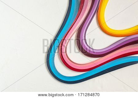 Bright multi-colored strips for quilling on a white background