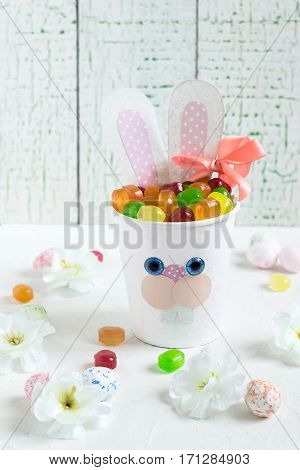 Paper cups in the form of funny Easter Bunny with candy. Homemade applique on paper cups. The idea for children gifts. DIY concept for the celebration of Easter. Selective focus vertical