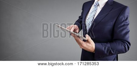 Businessman with tablet computer and gray background for copy
