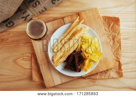 chips, crispy crackers of black bread with sesame and sticks and beer