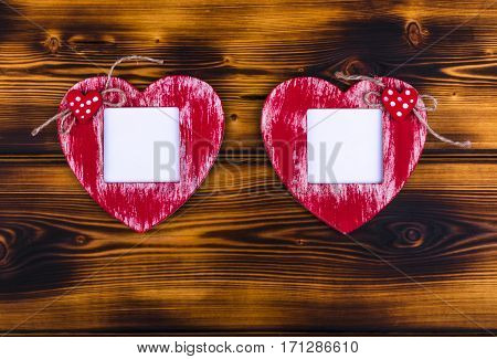Love card template with blank photo frame heart shaped on the red hearts on brunt wooden background