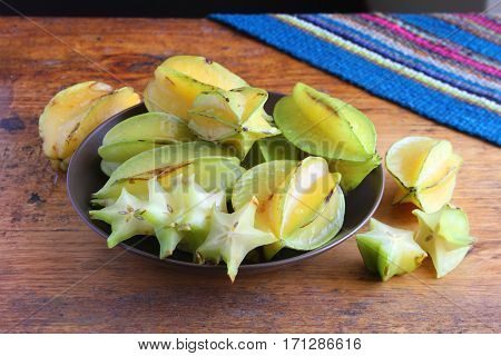 Bowl of star fruit or carambola on antique wooden table in Peru