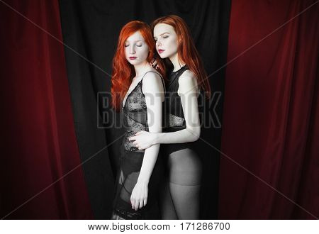 Two red sexual girl with blue eyes and pale skin on a black and red background. Women lesbian Long red hair. Fetish model. Look at the camera