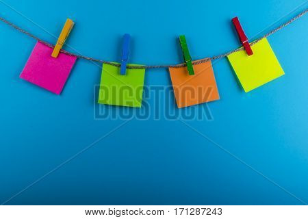 Clothespin hanging with blank photo papers on blue background texture