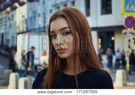 Portrait of a beautiful red-haired girl on a background of a city street. Close-up.