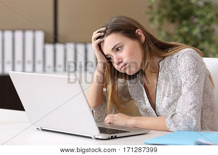 Frustrated intern trying to work on line with a laptop in a difficult assignment in a desktop with an office background