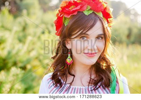 Pretty smiling girl in a garland of poppy flowers and national embroidered ethnic dress posing in small pines lit with sunset rays of light