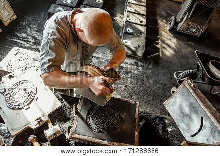 TELFORD UK - CIRCA 2013: A man makes a mold for pouring cast iron at Blists Hill Victorian Museum in Ironbridge UK