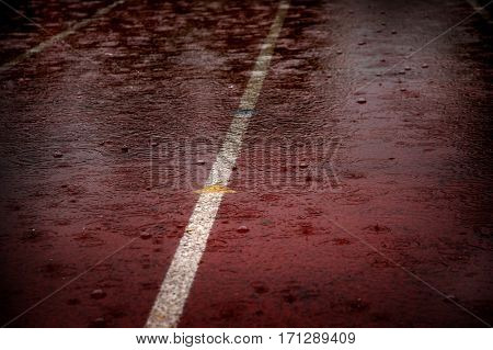 Heavy rain drops falling on race running track delaying competitions