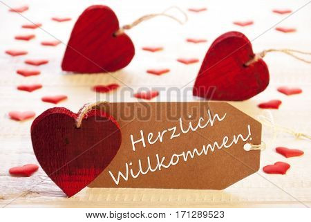 Label With German Text Herzlich Willkommen Means Welcome. Many Red Heart. Wooden Rustic Or Vintage Background.