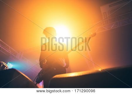 Rock band performs on stage. Guitarist plays solo. silhouette of guitar player in action on stage in front of concert crowd. Close-up. Dark background. Smoke. Light
