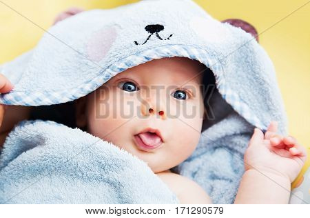 Cutest baby child after bath with towel on head. Adorable smiling baby boy!