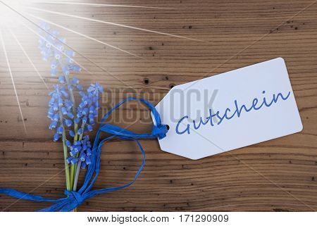 Label With German Text Gutschein Means Voucher. Sunny Blue Spring Grape Hyacinth With Ribbon. Aged, Rustic Wodden Background. Greeting Card For Spring Season