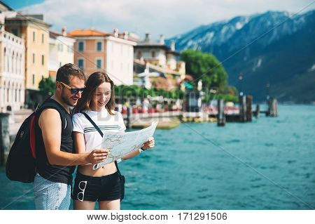 Travel Italy Europe. Smiling couple in love with a map at Lake Garda with mountains lake and town on the background. Lake Garda is the largest lake in Italy. Lifestyle Holidays and Travel Concept.