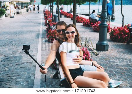 Tourist couple of lovers making selfie photo on motion camera at Lake Garda Italy Europe. Holidays and Travel Concept. Happy couple recording their trip with action camera.