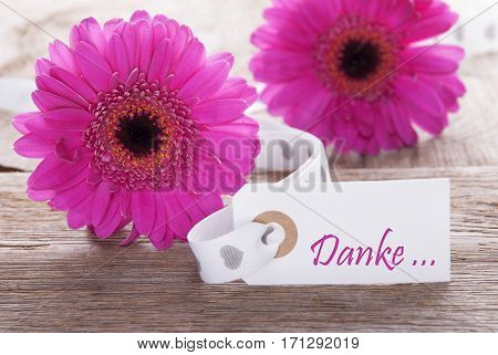 Label With German Text Danke Means Thank You. Pink Spring Gerbera Blossom. Vintage, Rutic Or Aged Wooden Background. Card For Spring Greetings.