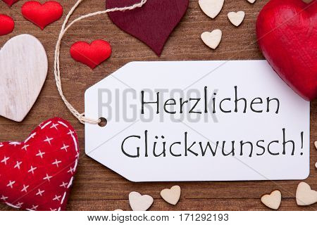 Label With German Text Herzlichen Glueckwunsch Means Congratulations. Red Textile Hearts On Wooden Background. Flat Lay With Retro Or Vintage Style