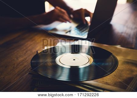 Old vinyl record and a collection of albums on wooden table with a hands of a man with working laptop in the background. Toned image
