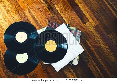 Old vinyl record and a collection of albums on wooden background