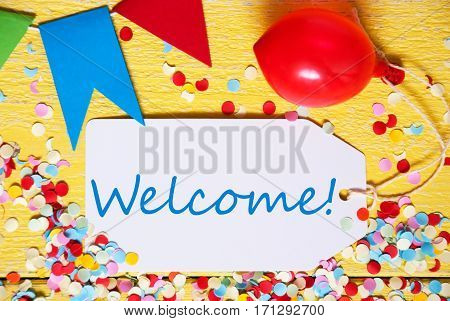White Label With English Text Welcome. Close Up Of Party Decoration Like Streamer, Confetti And Balloon. Flat Lay Or Top View. Yellow Wooden Background