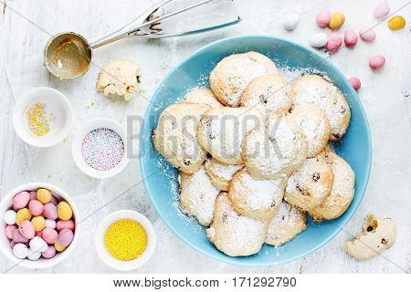 Delicious Easter cookies with chocolate candy eggs and colorful sugar sprinkles on white wooden background