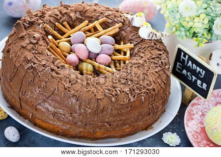 Easter bird nest cake - chocolate cake with pastel candy eggs in nest shape for Easter holiday party