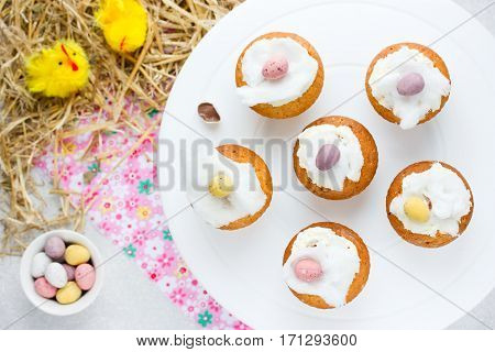 Easter birds nest cupcakes with chocolate candy eggs whipped cream and cotton candy