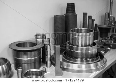 Industrial lathe tool and high precision cnc turning parts. high precision automotive machining mold and die part. CNC prosessed parts on table. Black and white.