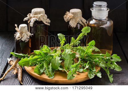 Medicinal plant dandelion. Dandelion leaves on a wooden board tincture and syrup in pharmaceutical bottles roots on wooden background. It is used for herbal medicine and healthy food