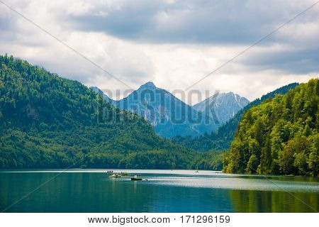 Blue Alpsee Lake In The Green Forest And Beautiful Alps Mountains. Fussen, Bavaria, Germany