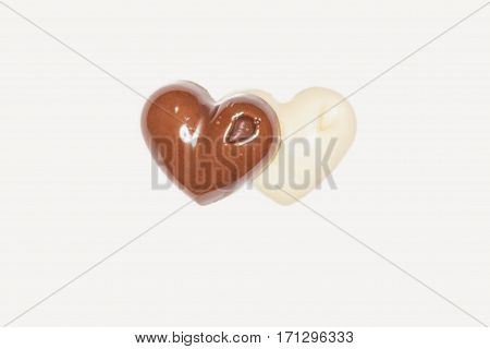 Close Up Of Two Pieces Of Dark And White Chocolate Having Heart Shape On A White Background