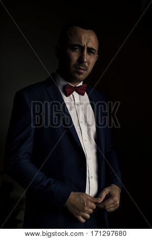 portrait of young stylish businessman in a blue jacket on a black background