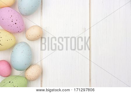 Pastel Speckled Easter Egg Side Border Against A White Wood Background