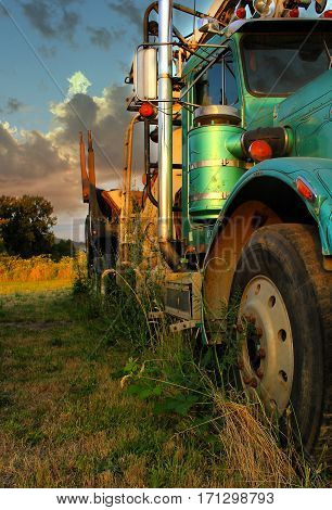 Side view of a green turquoise old vintage diesel logging truck with dramatic lighting and sky