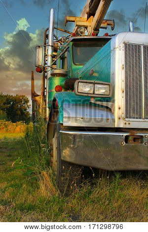 Side view of a green turquoise vintage diesel logging truck with dramatic lighting and sky
