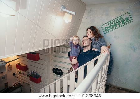 mom dad and daughter sit on the stairs at the cafe, Dad keeps daughter in her arms