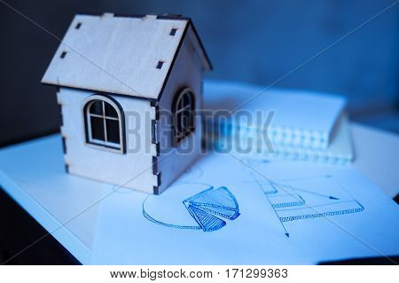 Toy wooden house and schedules profit growth. Concept