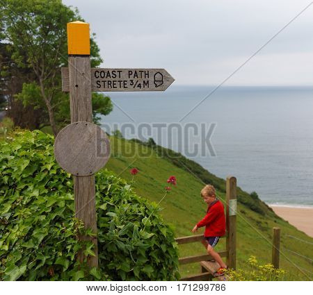 Strete, Devon, UK, June 1, 2016. Editorial photograph of wooden route sign and child on the South West Coast Path in Stoke Fleming, Devon. The South West Coast Path National Trail follows 630 miles of coastline around Devon and Cornwall.