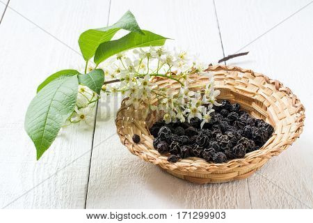 Medicinal plant bird cherry (Prunus padus). Flowering branches and dried berries in a wicker bowl on a white wooden background. Selective focus
