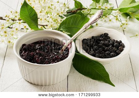 Medicinal plant bird cherry (Prunus padus). Flowering branches dried berries and jam on a white wooden background