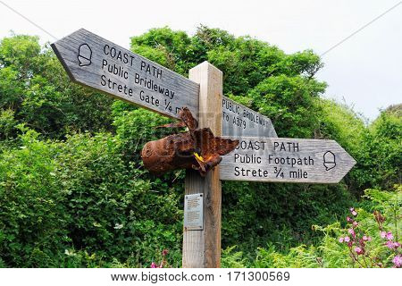 Strete, Devon, UK, June 1, 2016. Editorial photograph of wooden route sign on the South West Coast Path in Strete, Devon, with attached piece of ordnance from Exercise Tiger, one of the Normandy landing rehearsals in the area.