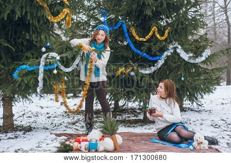 The girls sit near trees in winter on snow and drinking tea from a thermos and circle